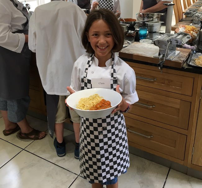 Child holding pasta dish