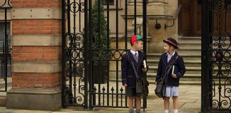 Two schoolchildren standing at school gate